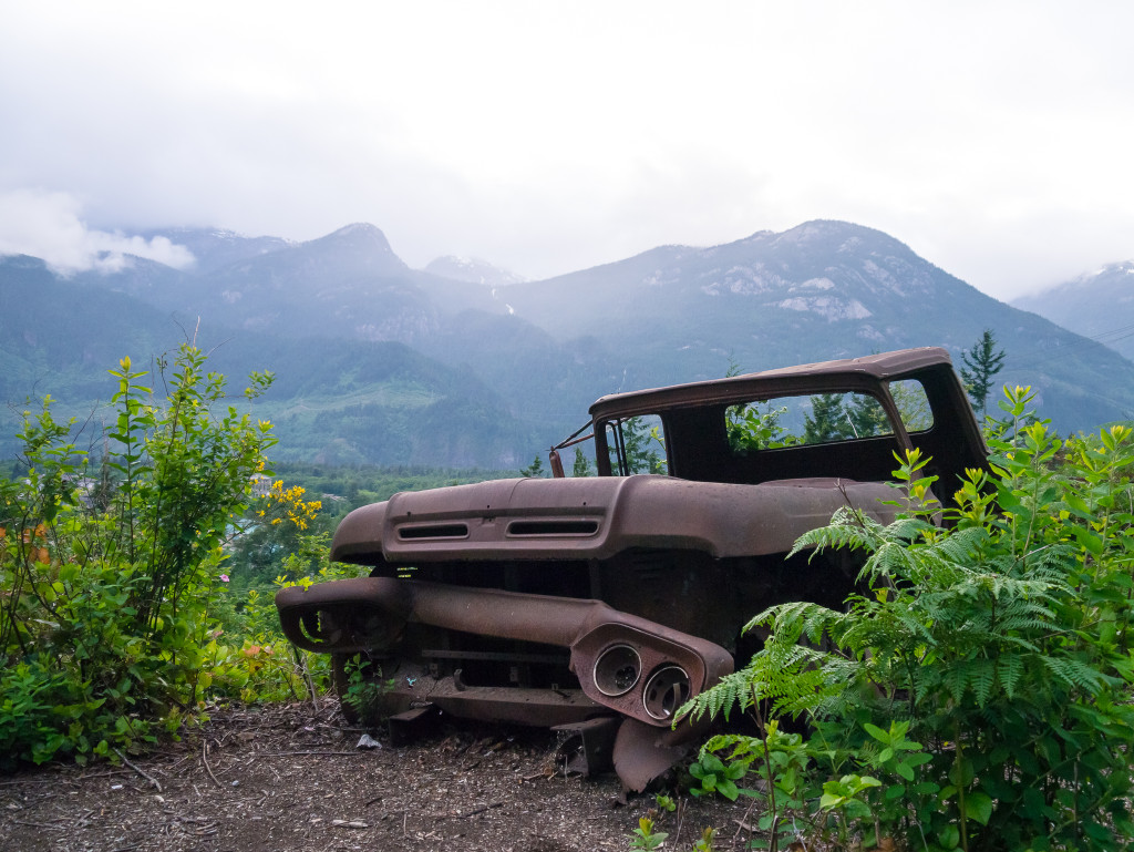 A rusty truck on a trail at the Smoke Bluffs, surrounded by green trees with mountains in the background.