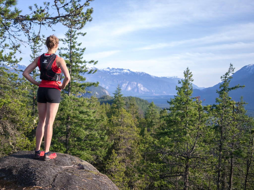 A female hiker standing on a rock and taking in the view at the Brohm Lake viewpoint in Squamish, with dense green trees covering the ground and mountains in the background.