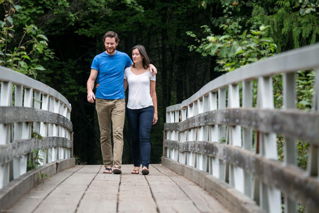 A man and woman walk arm in arm across a pedestrian bridge.