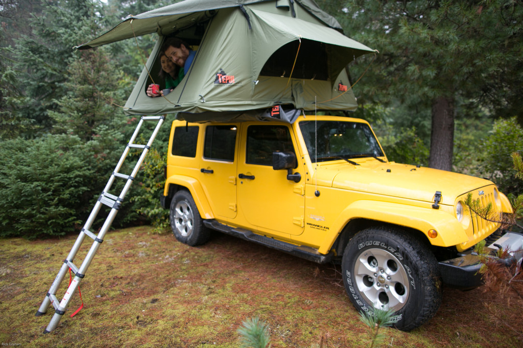 A man and woman lay in a fold-out roof-tent on top of a yellow Jeep