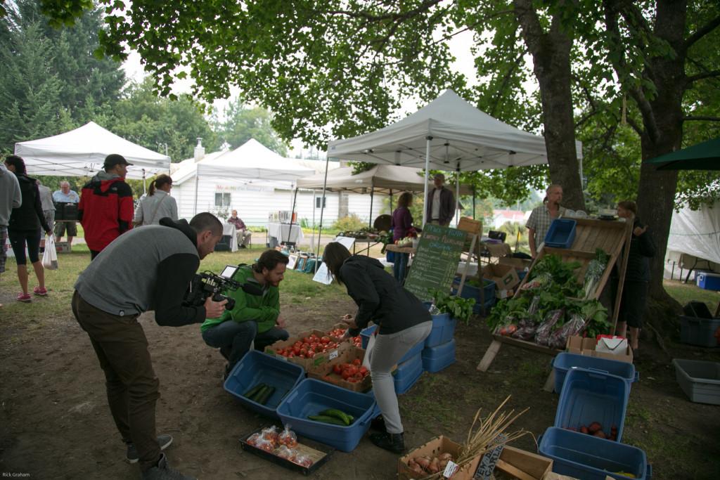 A man films a busy outdoor farmer's market.