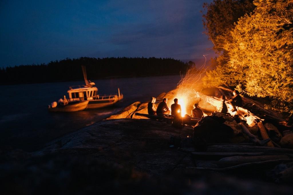 Sitting around the campfire at Nimmo Bay Resort. Photo: @jeremykoreski