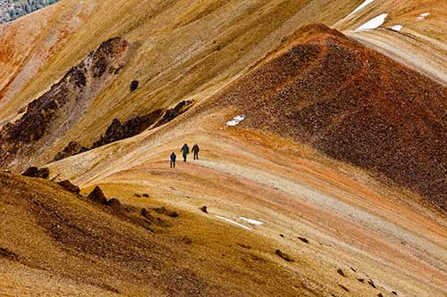 Three hikers walking through the Rainbow Range in Tweedsmuir Provincial Park.