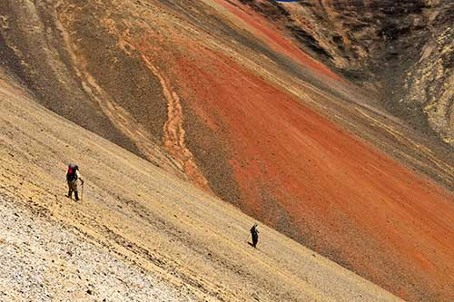 Two hikers using walking poles as they hike into the orange core of Rainbow Volcano.