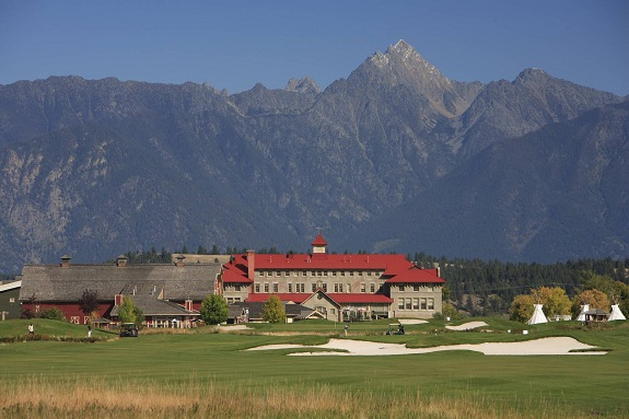 A sprawling resort and golf course nestled at the base of a rocky mountain range.