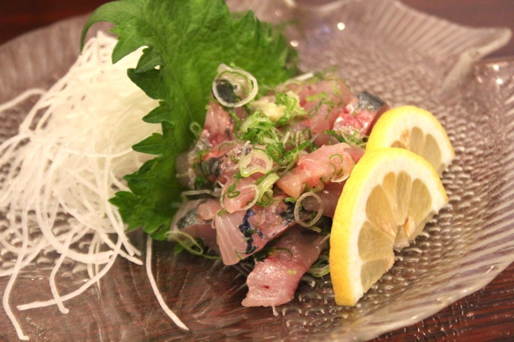 A colourful plate of Tataki, garnished with lemons.