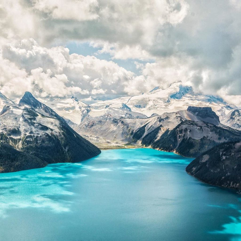 Turquoise waters run through snow-capped mountains.