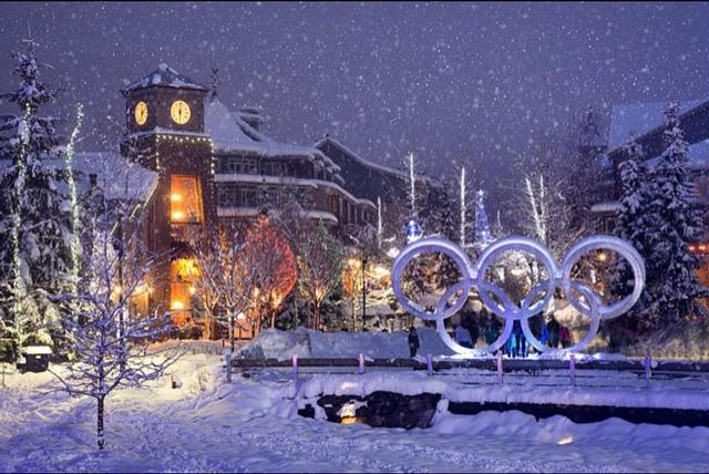Snow falls softly on a quiet village with a lit up display of the Olympic circles.