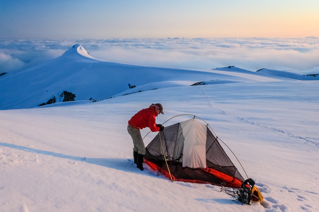 A woman pitches a tent at the summit of a snow covered mountain.