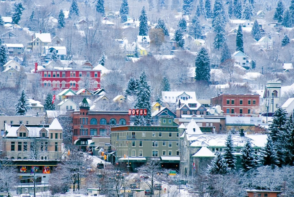 Quaint, colourful buildings are nestled in a snowy landscape.