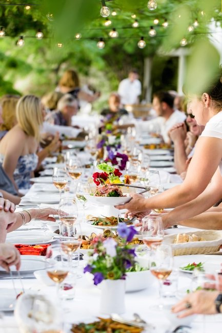 A large group dines alfresco at a beautifully set table.