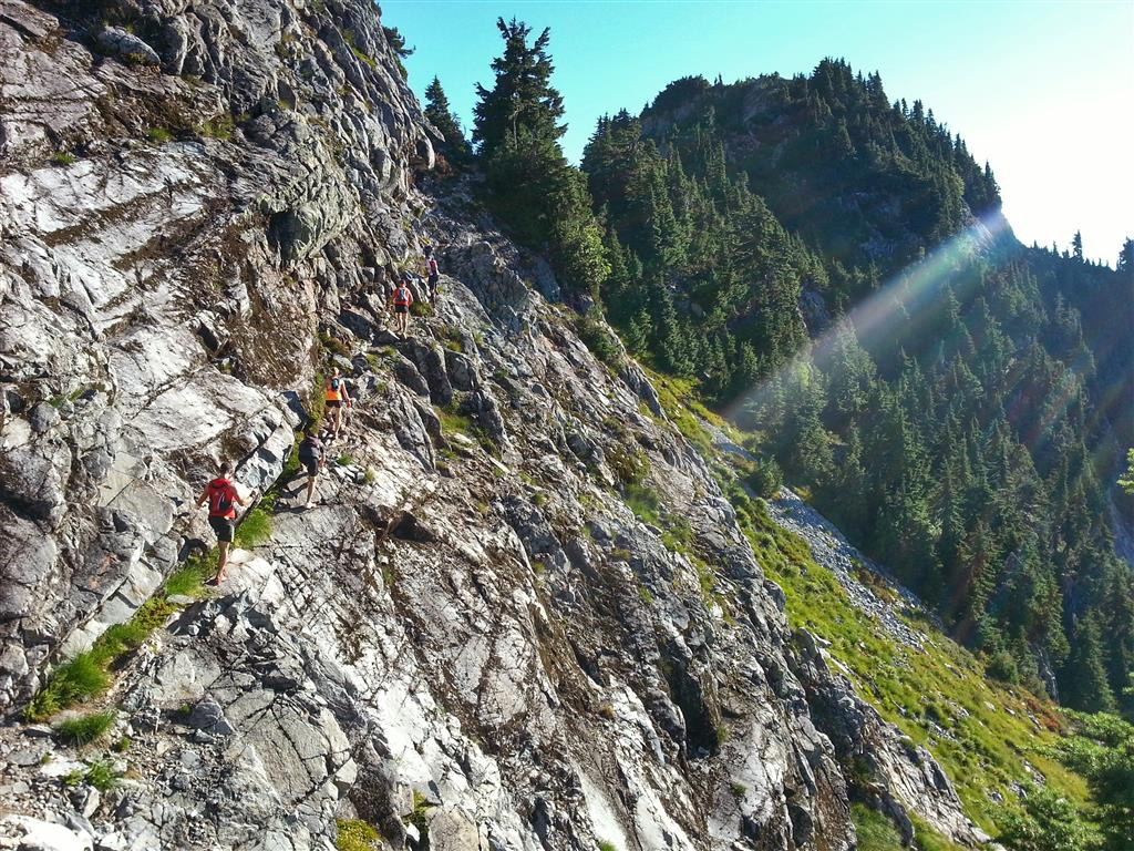 Trail runners make their way up a rocky cliff face on a sunny day.