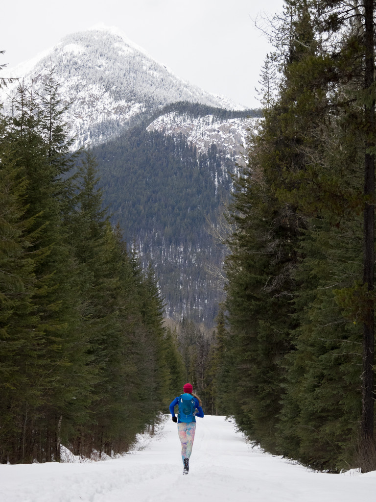 A woman wearing a backpack runs down a snow-covered trail lined with pine trees.