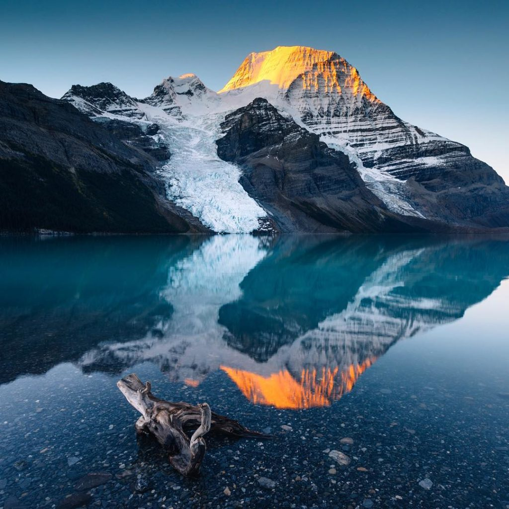 Placid waters reflect glacial mountains at sunset.