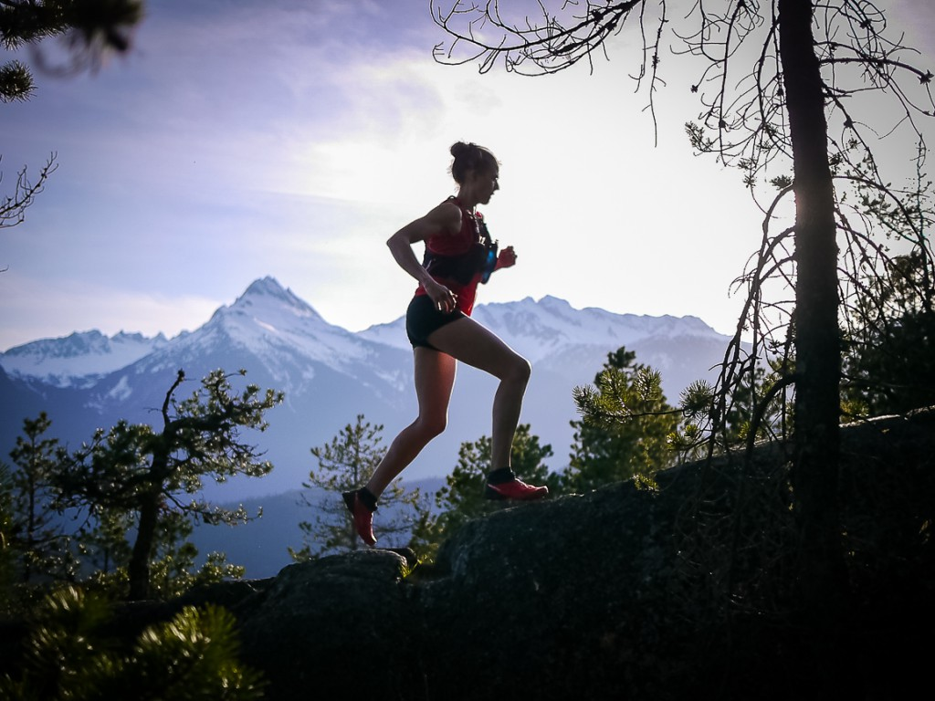 A trail runner conquers a steep trail with view of a snow-covered mountains.