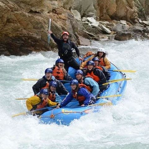 A group of men and women enjoy a white water rafting adventure.