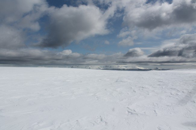 A desolate, snowy landscape under a cloudy sky.