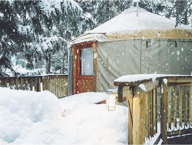 A winterized yurt is covered in a fresh snowfall.