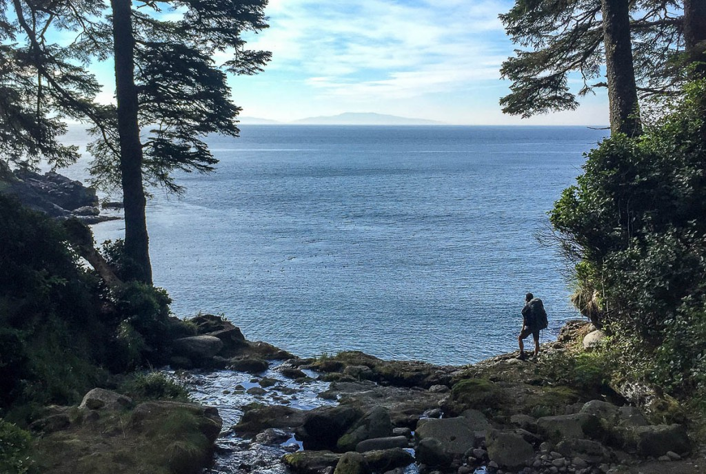 A hiker stops to take in the view of the Pacific Ocean along the Juan de Fuca Marine Trail.
