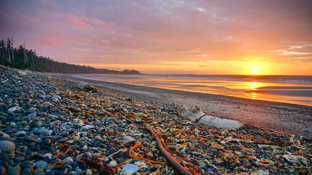 The sunsets over a beach with a rugged terrain.