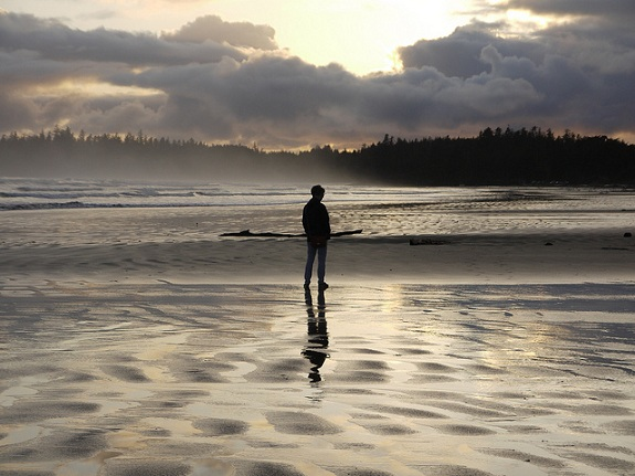Silhouette of a man walking across a windswept beach at sunset.
