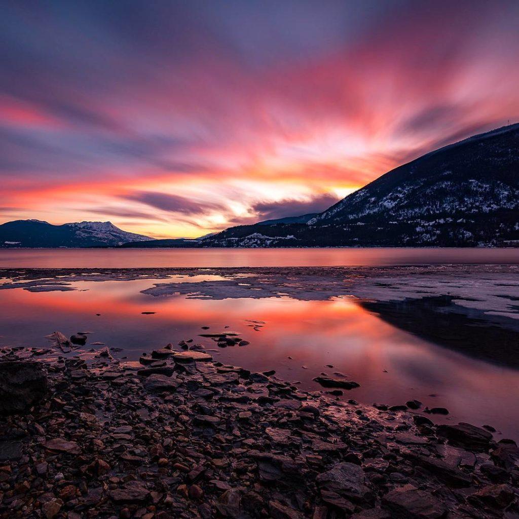 A stunning orange, pink, and purple sunset over a still lake.