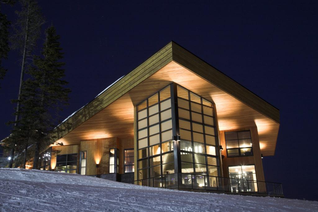A modern ski resort under an evening sky.