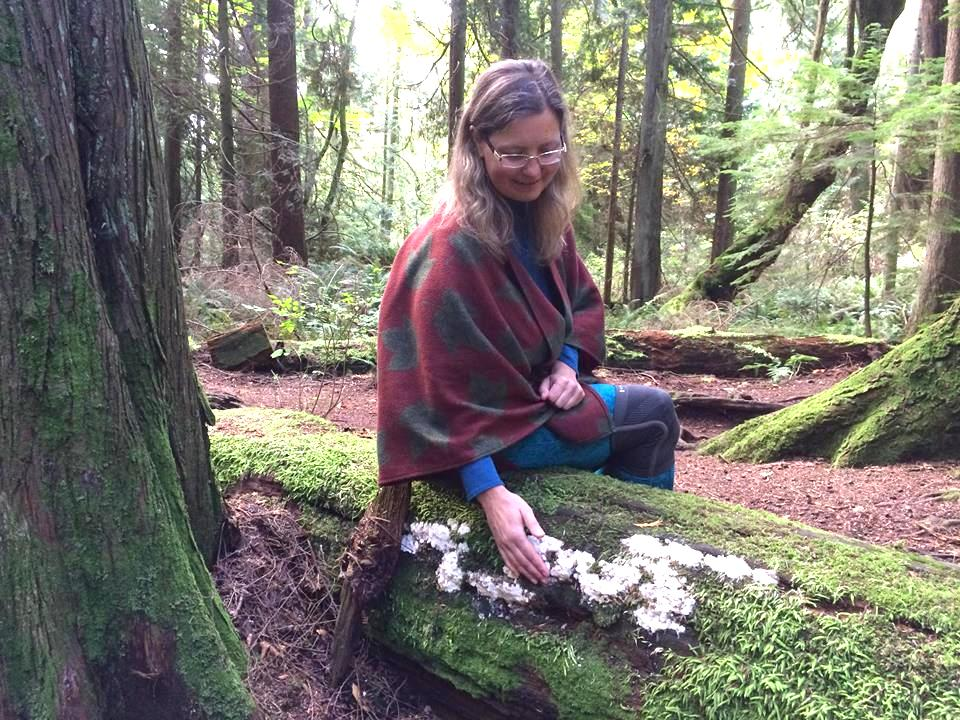 A woman sits on a moss-covered fallen log in the forest.