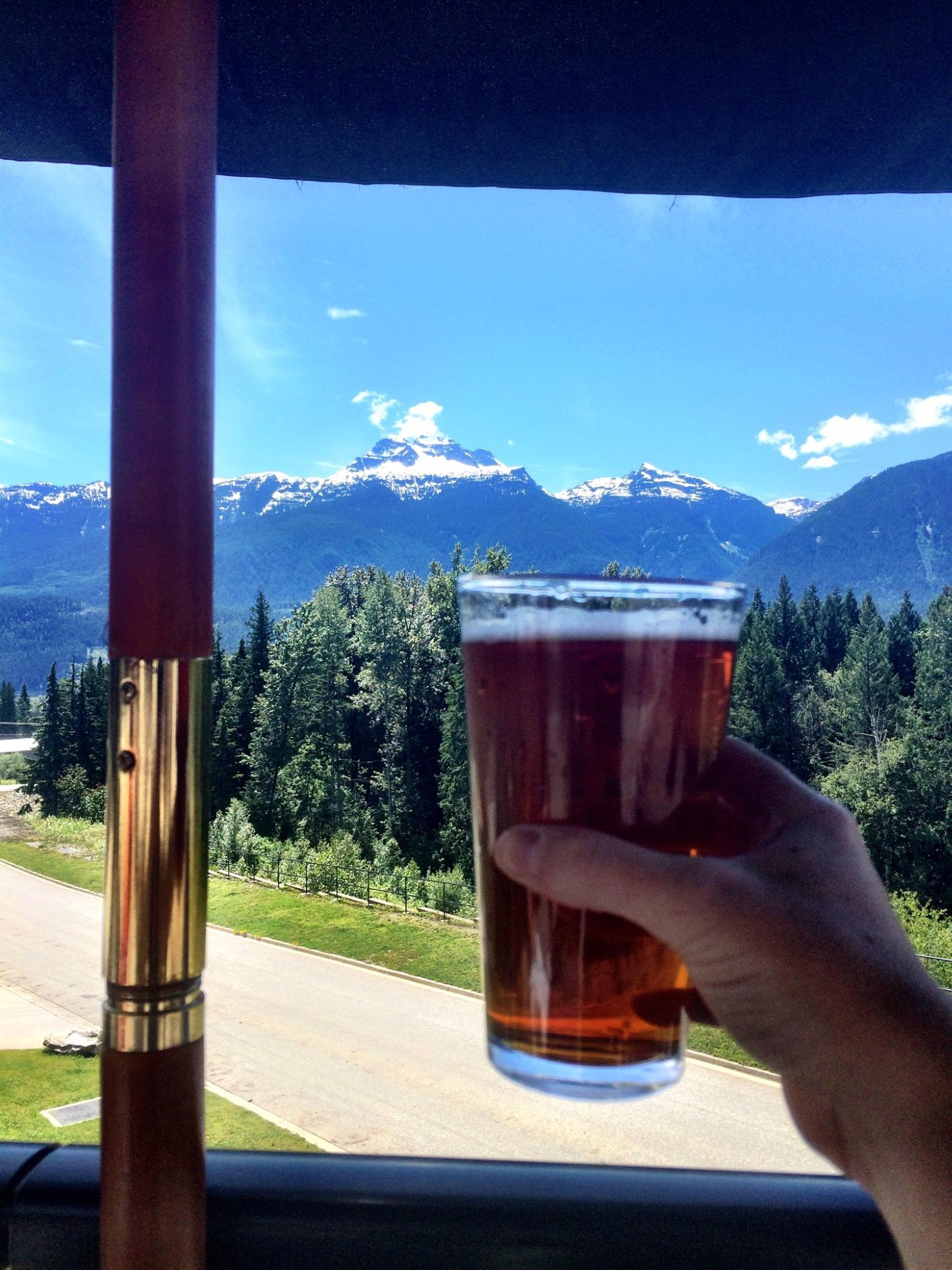A hand holds up a full pint glass in front of a mountainous landscape.