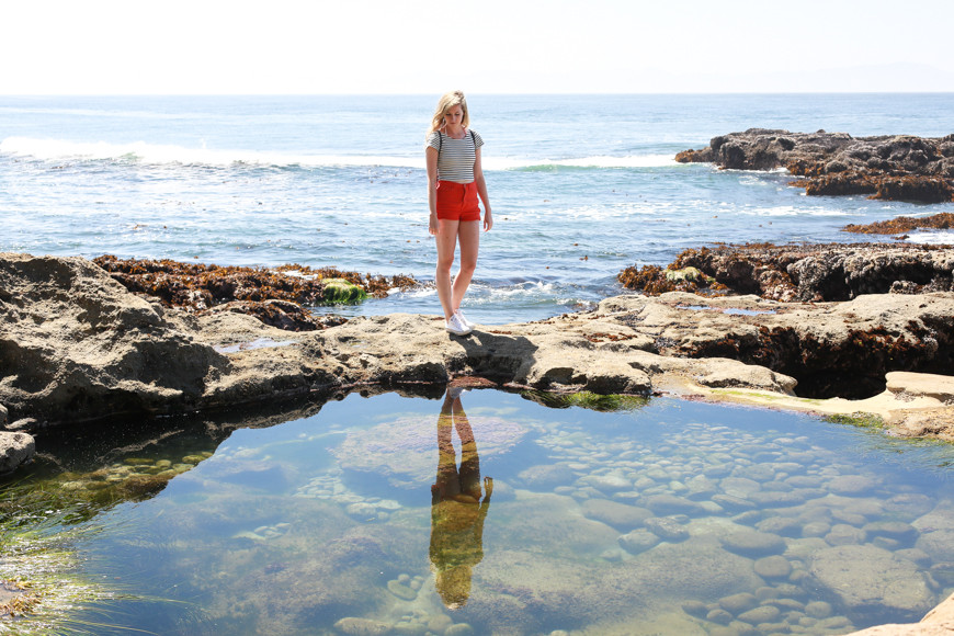 A woman stops to look at her reflection in a tidal pool.