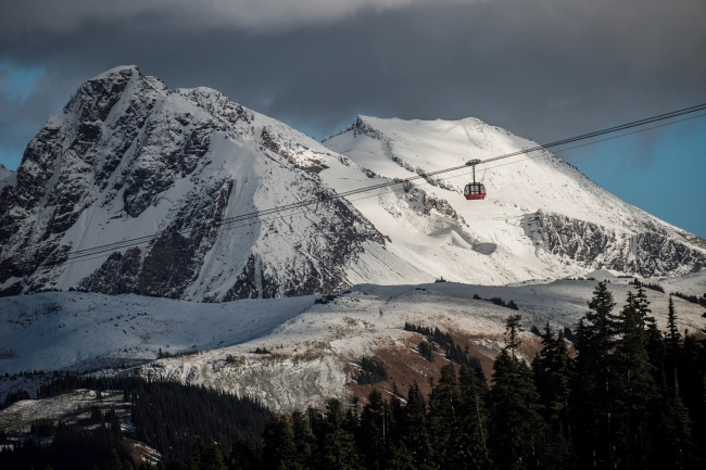 A gondola travels past snow covered mountains.
