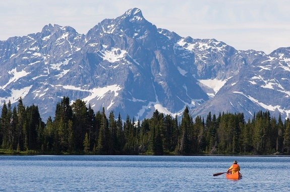 A man in a canoe paddles towards snow-capped mountains.