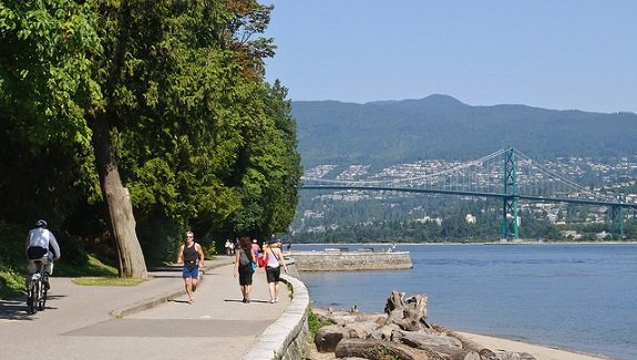 Groups of people walk, jog, and bike along the Stanley park Seawall.