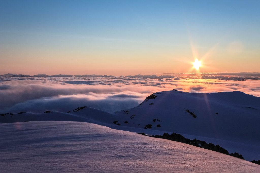 A stunning sunset over snow-covered mountains peeking above the clouds.