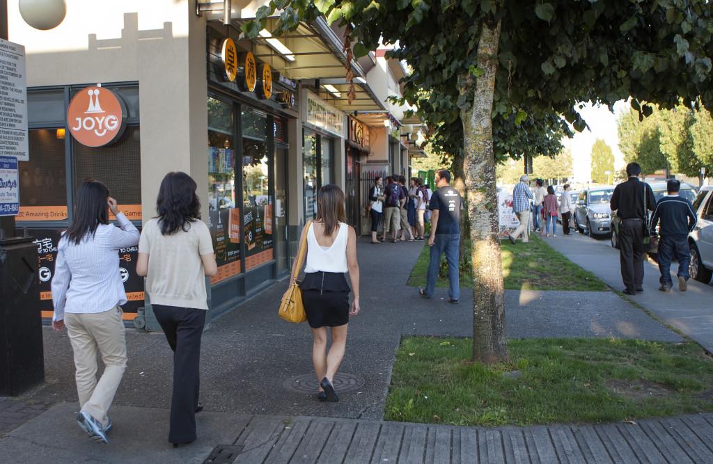 Pedestrians walk down a tree-lined sidewalk on a sunny day.