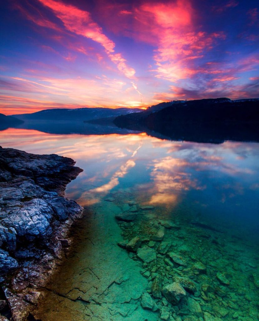 A multicolored sunset is reflected in a glass-like lake.