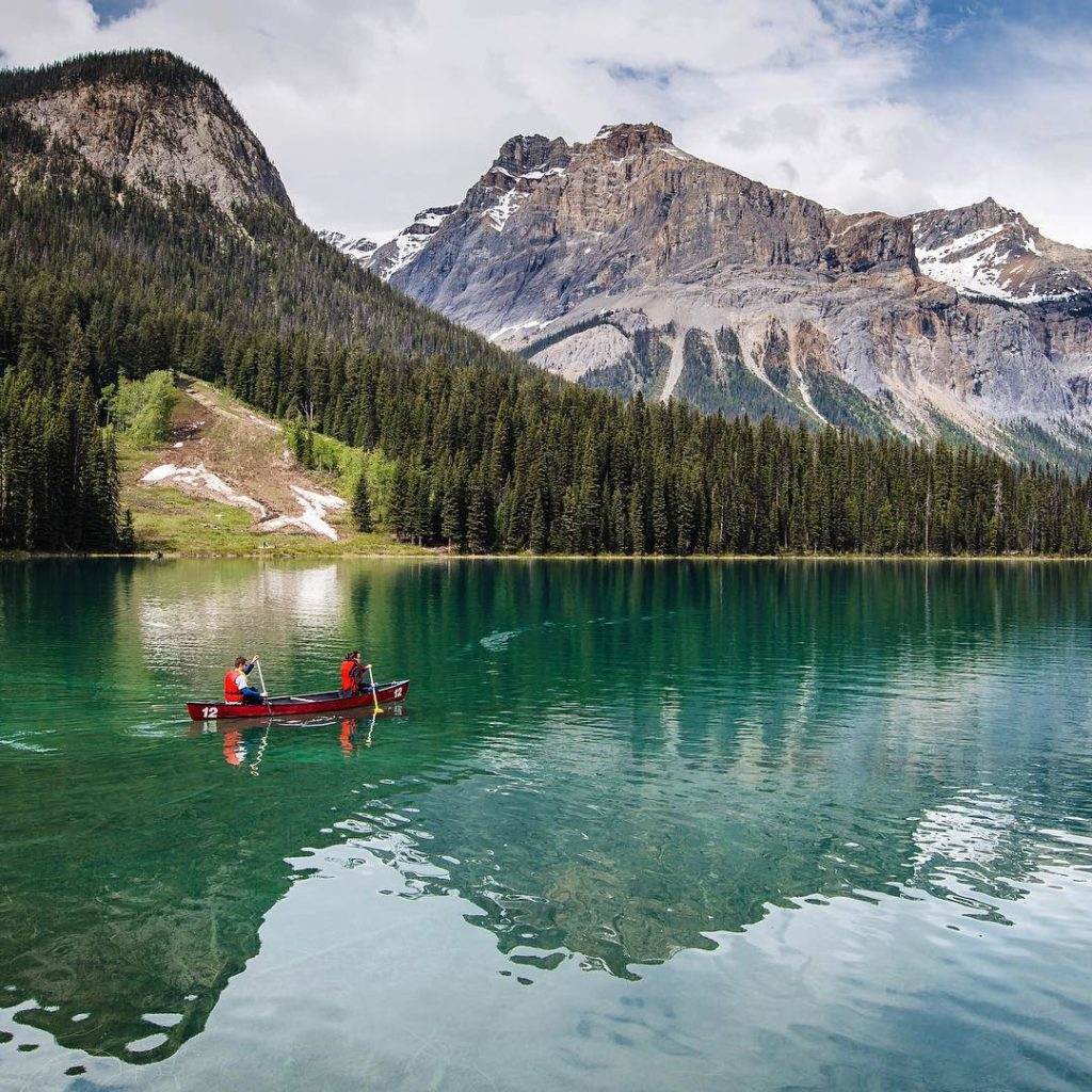 Canoeing through Emerald Lake, lined with dense vegetation and snow-capped mountains.
