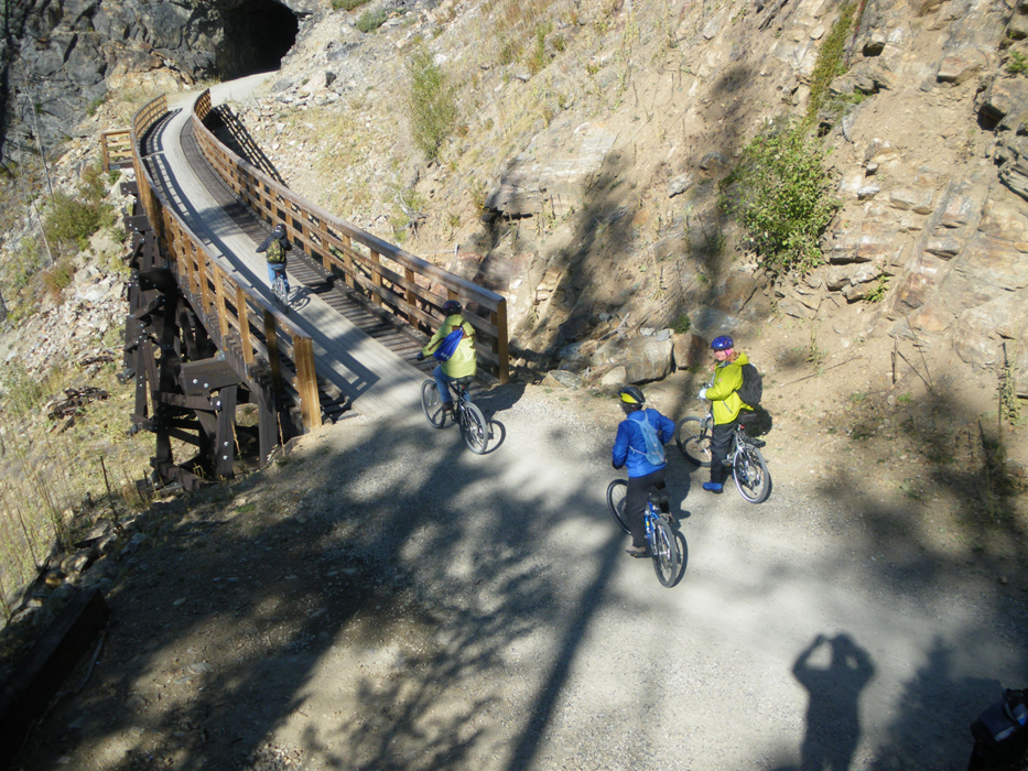 A group of cyclists traverse a bridge in a rocky landscape.