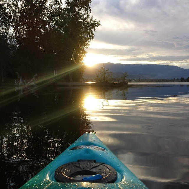 A kayak travels through quiet waters at sunset.