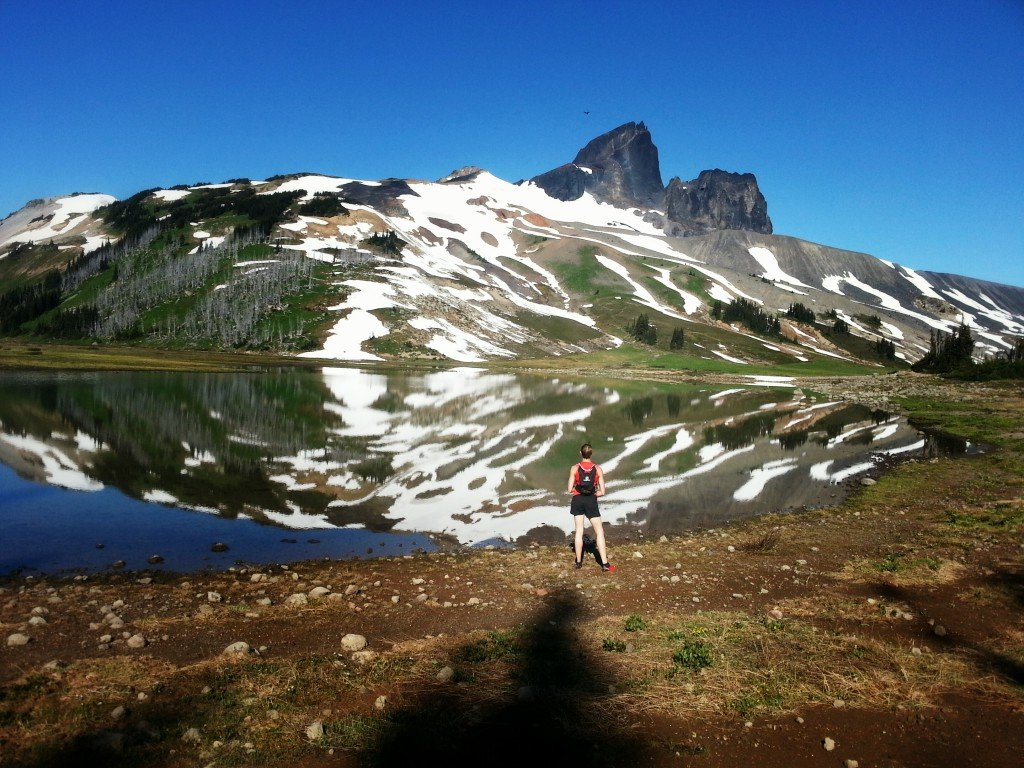 A hiker pauses to take in the reflection of a snow covered mountain in a still pond.