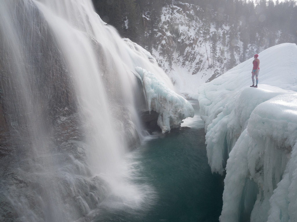 A woman stands at the edge of a snowy cliff, looking out at a stunning waterfall.