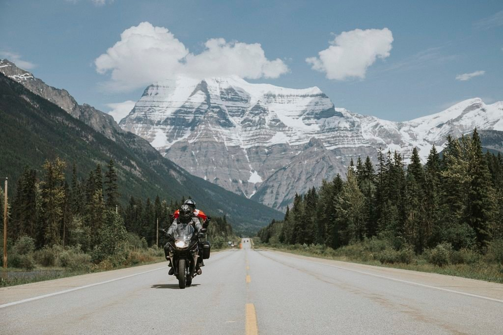 A motorcycle travels down the highway, with snow-capped mountains in the background.