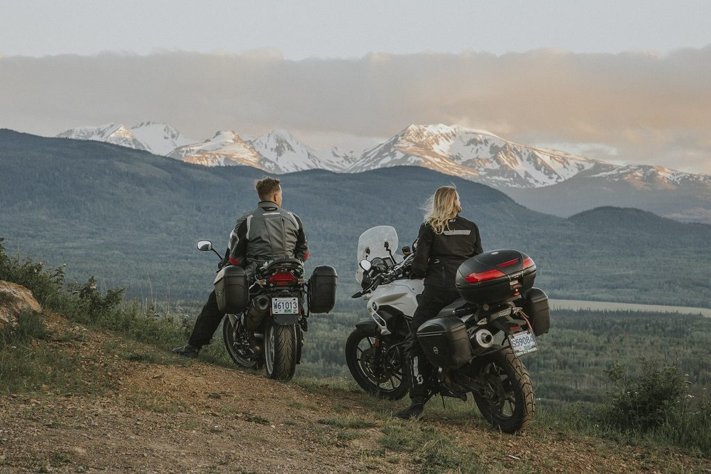 A woman and a man pull over on their motorcycles to take in the view of snow-covered mountains.