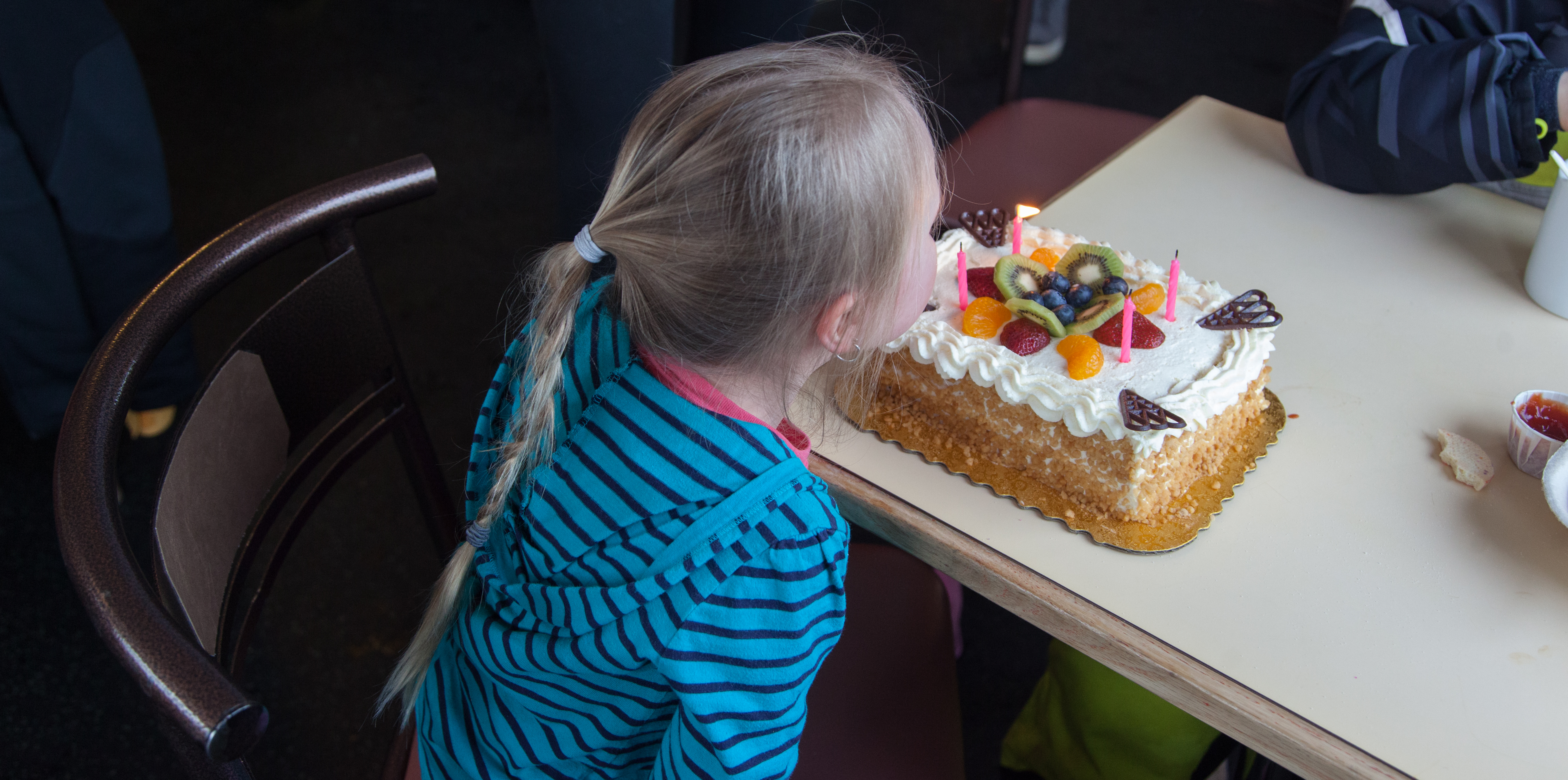 Girl blowing out birthday cake at Shames Mountain in Terrace, BC