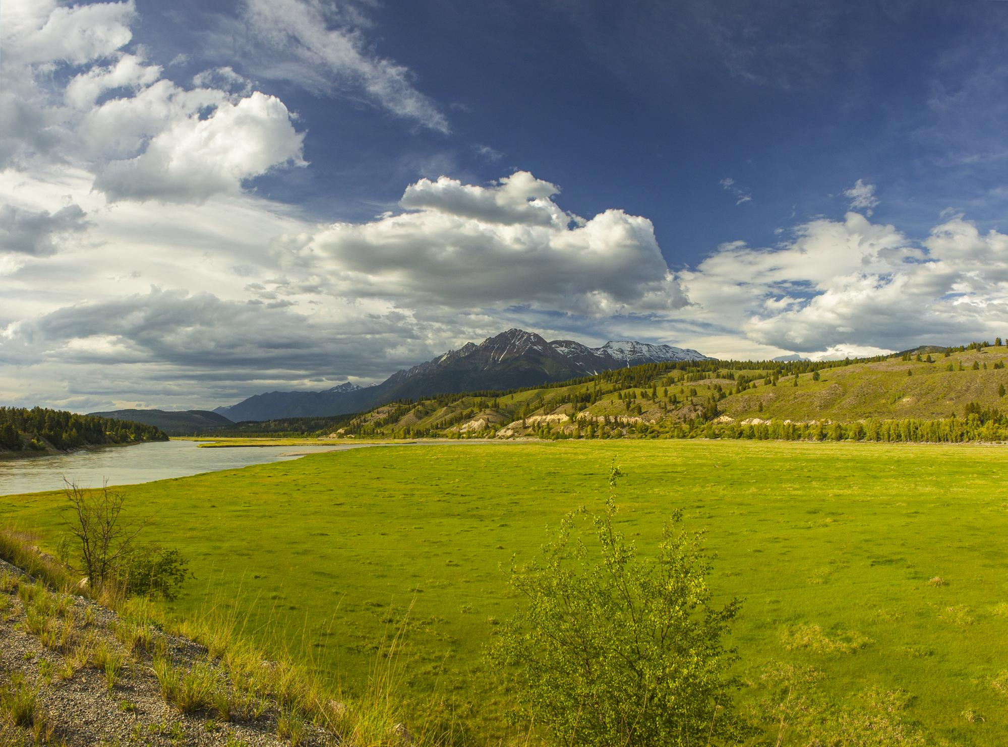 A lush, sprawling landscape is nestled between a river and a mountain range.