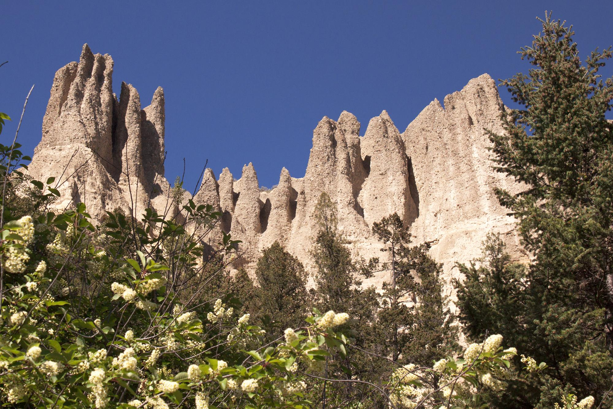 Looking up at a rock formation under a clear blue sky.