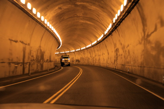 A jeep drives through a glowing highway tunnel.