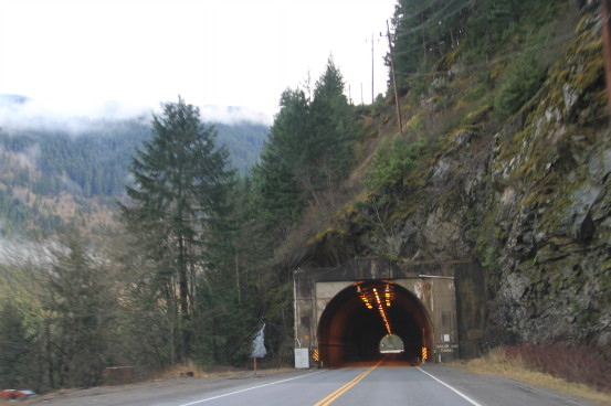 View of a highway tunnel nestled at the base of a rocky hill.