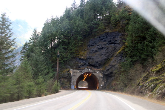 Approaching a highway tunnel that cuts through a rocky cliff dotted with pine trees.