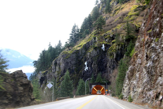 A highway tunnel travels through a rocky mountain.